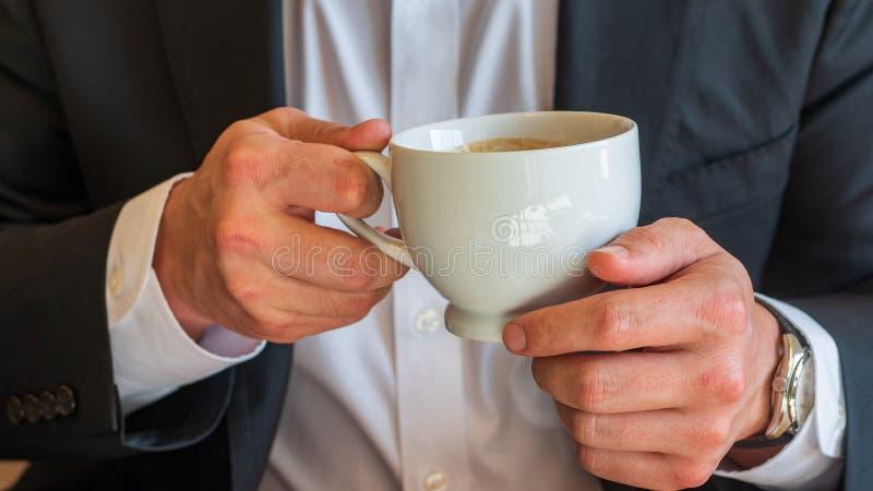 Homem que guarda uma xícara de café com o creme e a placa branca pequena, vestidos na camisa de vestido branca e no terno de negó fotografia de stock royalty free