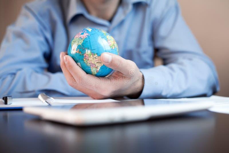 Homem que guardara o globo Negócio global foto de stock