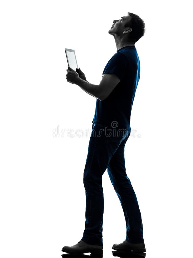 Homem que guardara a tabuleta digital que olha acima a silhueta fotos de stock