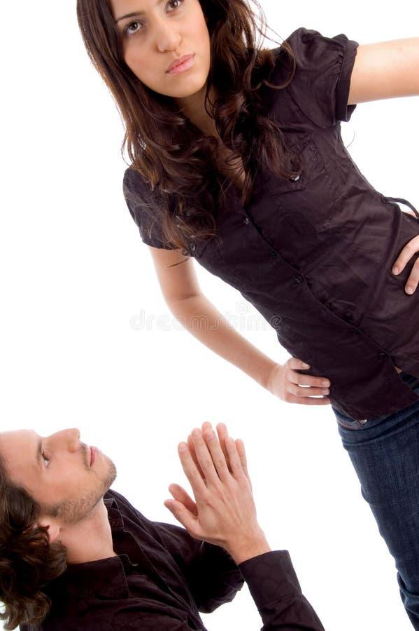 Homem que implora na frente da mulher foto de stock