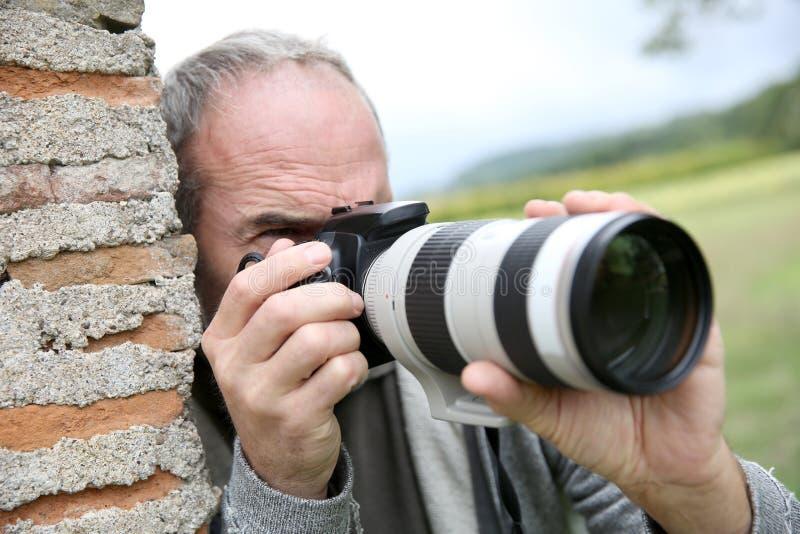 Homem que inclina-se na parede que toma as imagens exteriores imagem de stock