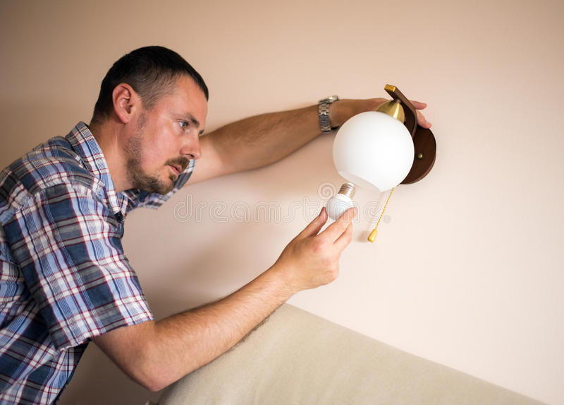 Homem que instala o bulbo imagens de stock