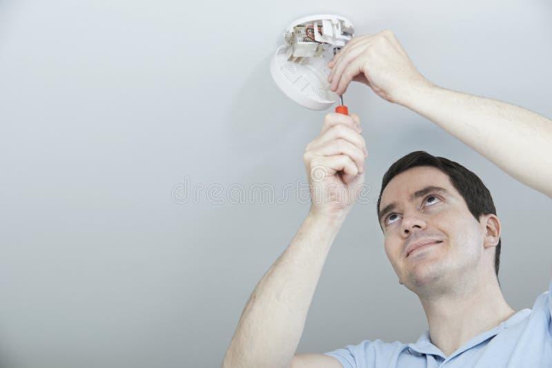 Homem que instala o detector de monóxido do fumo ou de carbono imagem de stock