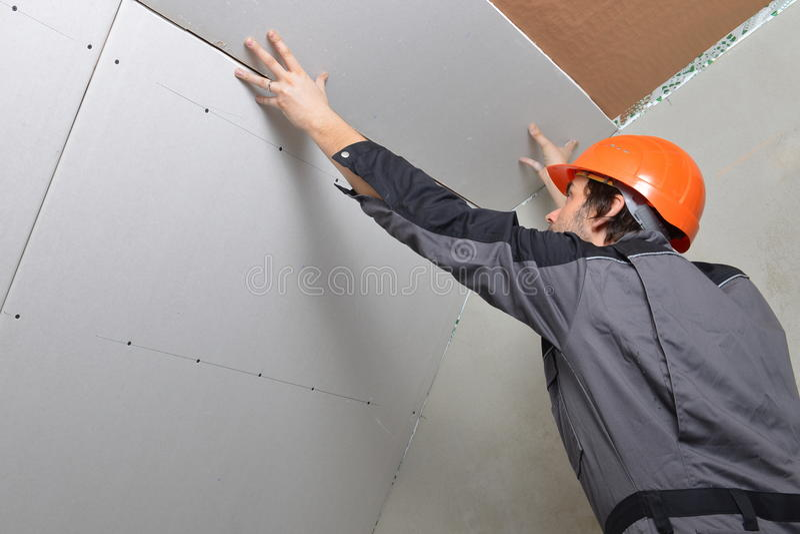 Homem que instala o drywall imagem de stock