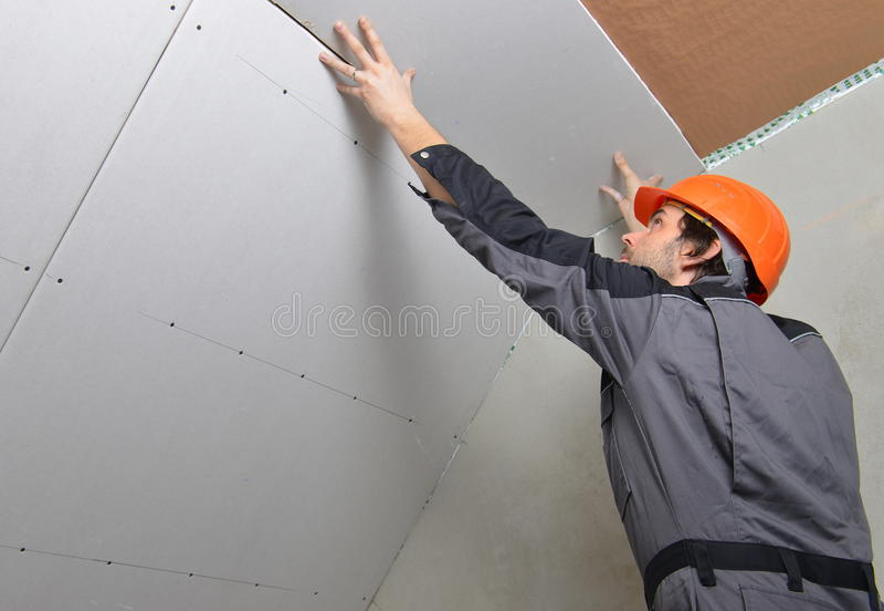 Homem que instala o drywall foto de stock royalty free