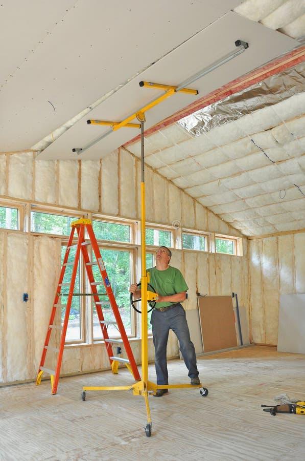 Homem que instala o drywall no teto imagem de stock royalty free
