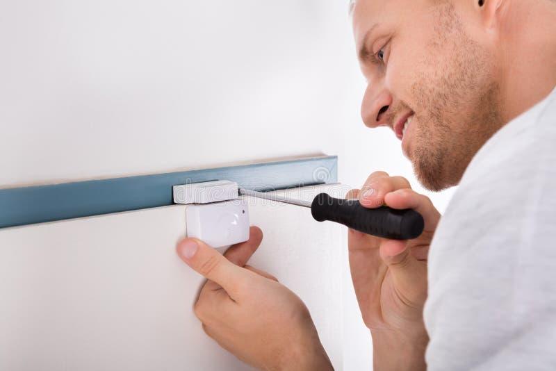 Homem que instala o sensor da porta do sistema de segurança imagens de stock royalty free