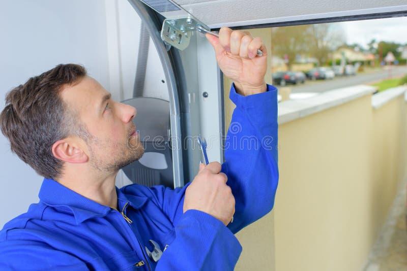 Homem que instala a porta da garagem foto de stock