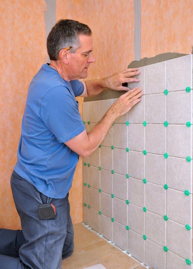 Homem que instala a telha cerâmica imagens de stock