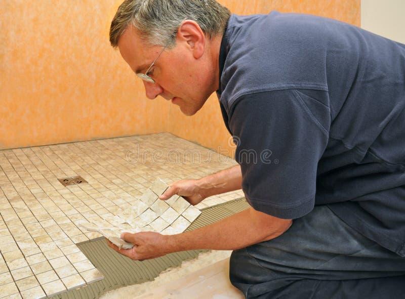 Homem que instala a telha cerâmica no banheiro fotografia de stock