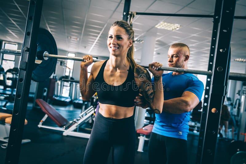 Homem que instrui uma mulher em um gym fotos de stock royalty free
