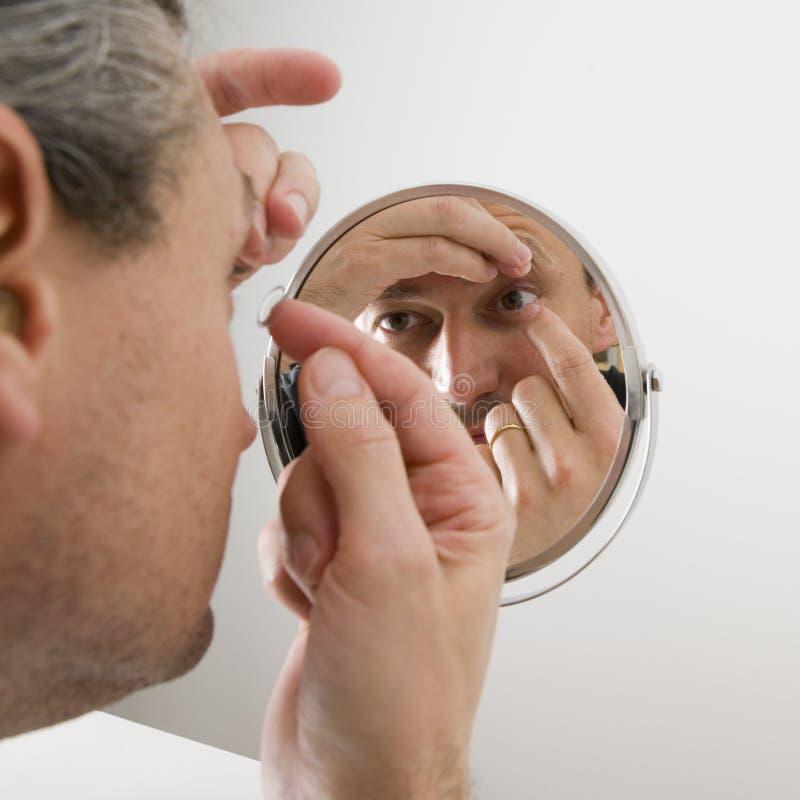 Homem que introduz uma lente de contato imagens de stock