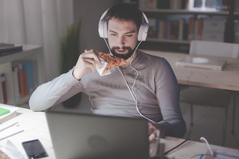 Homem que jantam em casa e trabalhos em rede imagem de stock royalty free