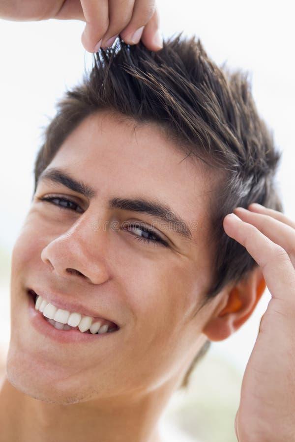 Homem que joga com sorriso do cabelo fotos de stock