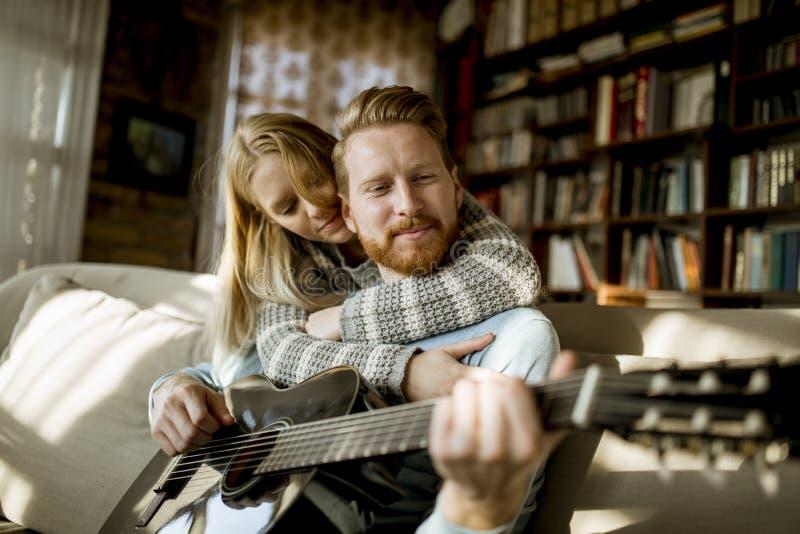 Homem que joga a guitarra acústica no sofá para sua mulher bonita nova foto de stock royalty free