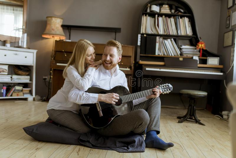 Homem que joga a guitarra acústica para a mulher bonita nova imagem de stock royalty free
