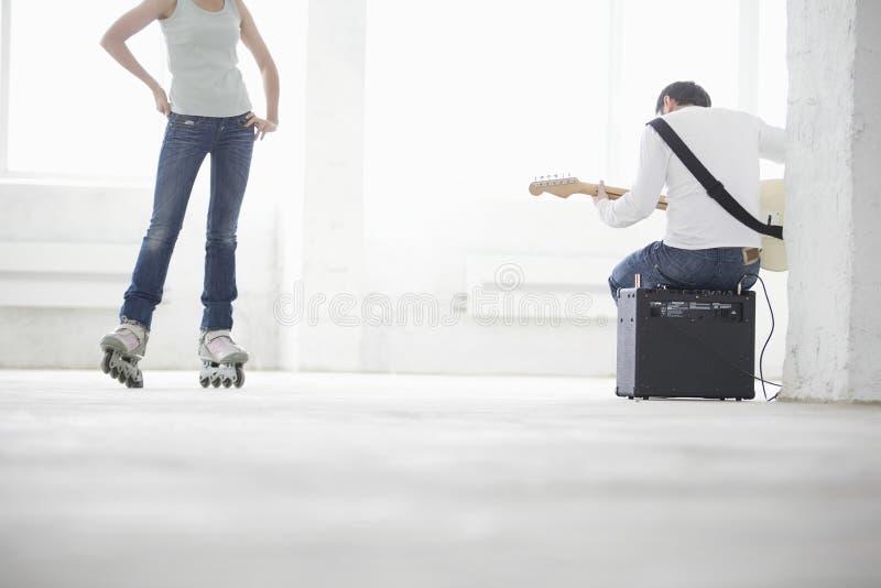 Homem que joga a guitarra elétrica com a mulher que veste o patim Inline em W fotografia de stock royalty free