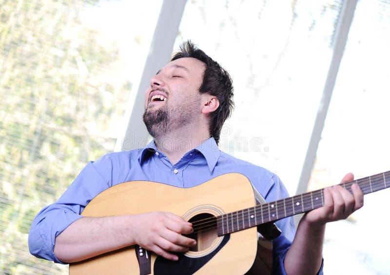 Homem que joga a guitarra interna imagens de stock royalty free