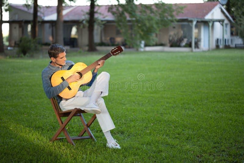 Homem que joga a guitarra no gramado foto de stock
