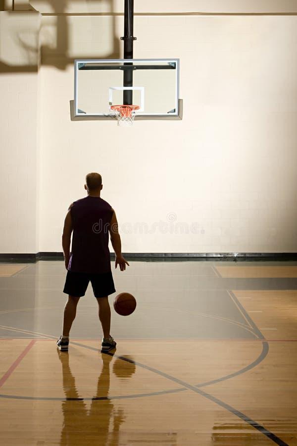 Homem que joga o basquetebol foto de stock