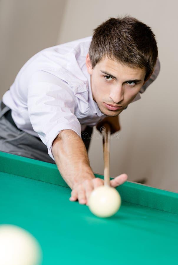 Homem que joga o bilhar no clube de jogo foto de stock