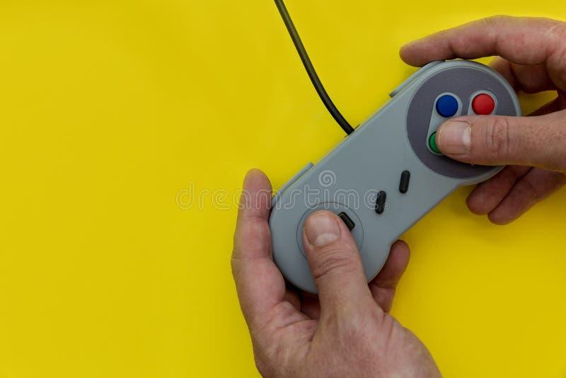 Homem que joga o jogo de vídeo com fundo do amarelo do controlador imagens de stock royalty free