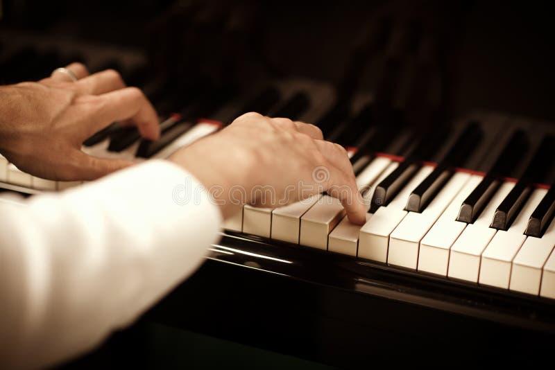Homem que joga o piano foto de stock