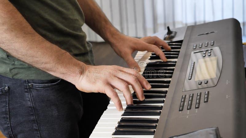 Homem que joga o piano bonde ou o teclado eletrônico fotografia de stock