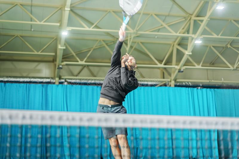 Homem que joga o tênis na corte tournament o atleta que salta com uma raquete em suas mãos imagens de stock royalty free