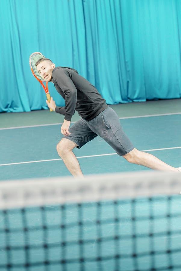 Homem que joga o t?nis o atleta dos esportes bate uma raquete na corte imagens de stock royalty free