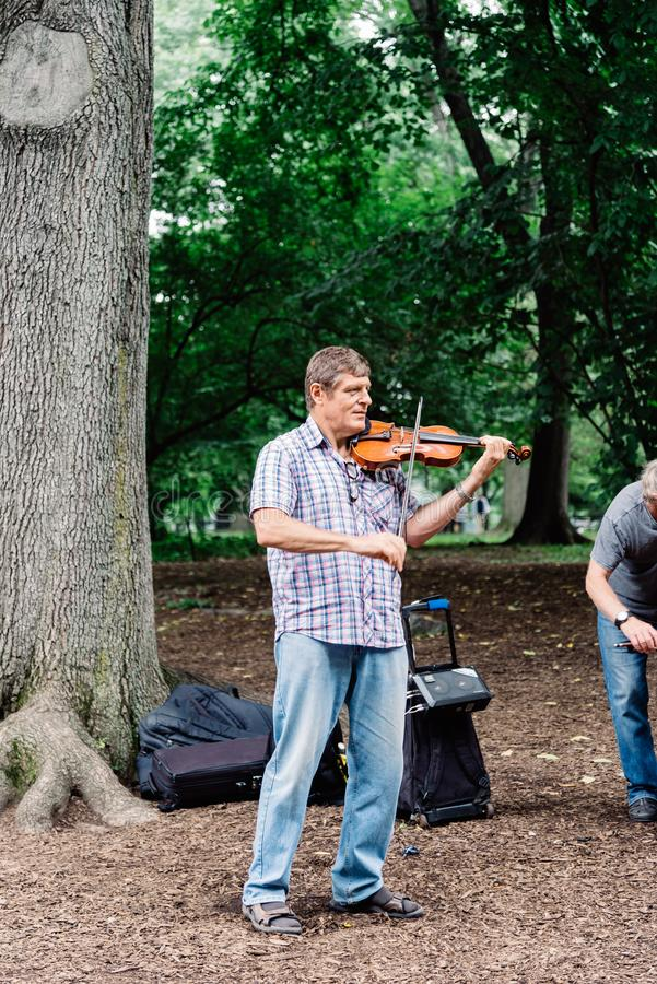 Homem que joga o violino no Central Park em New York fotografia de stock royalty free