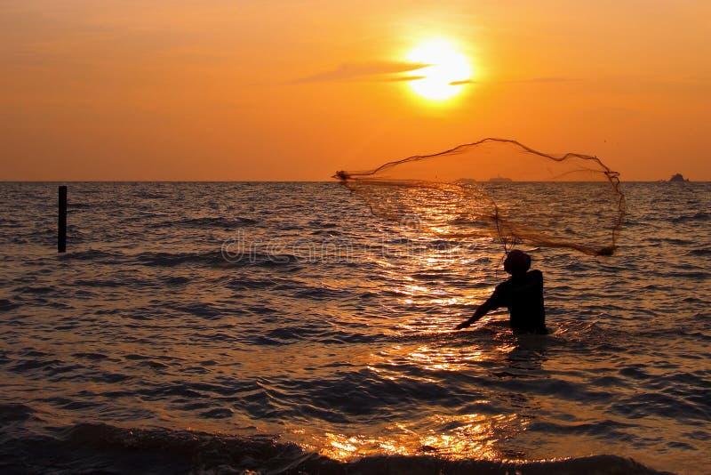 Homem que joga a rede de pesca imagens de stock