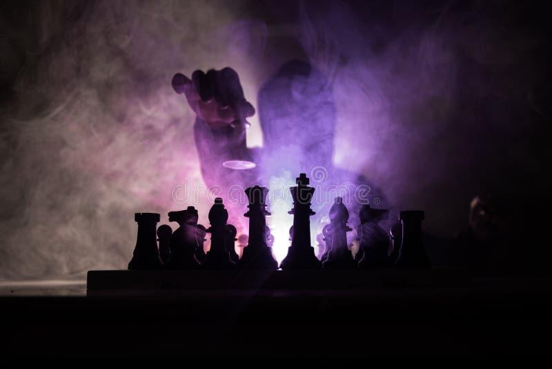 homem que joga a xadrez A silhueta borrada assustador de uma pessoa no tabuleiro de xadrez com xadrez figura Fundo nevoento tonif fotografia de stock royalty free