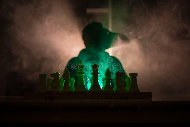 homem que joga a xadrez A silhueta borrada assustador de uma pessoa no tabuleiro de xadrez com xadrez figura Fundo nevoento tonif imagem de stock