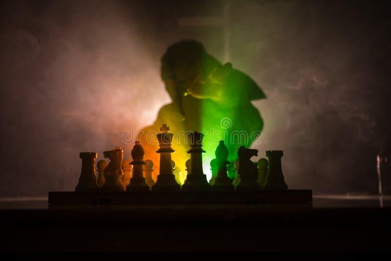 homem que joga a xadrez A silhueta borrada assustador de uma pessoa no tabuleiro de xadrez com xadrez figura Fundo nevoento tonif imagens de stock