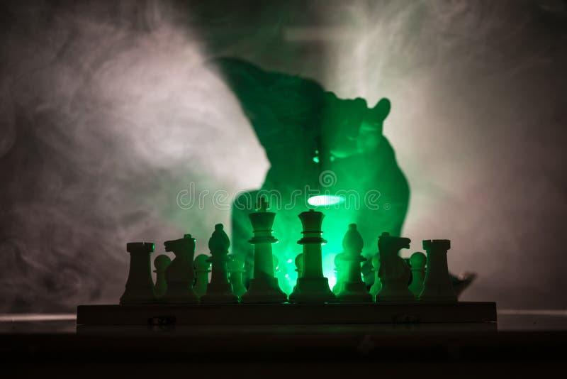 homem que joga a xadrez A silhueta borrada assustador de uma pessoa no tabuleiro de xadrez com xadrez figura Fundo nevoento tonif imagem de stock royalty free