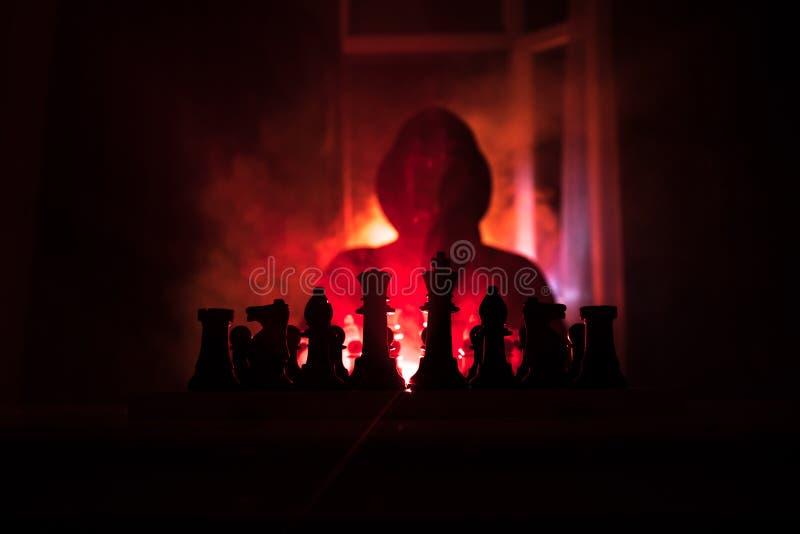 homem que joga a xadrez A silhueta borrada assustador de uma pessoa no tabuleiro de xadrez com xadrez figura Fundo nevoento tonif imagens de stock royalty free