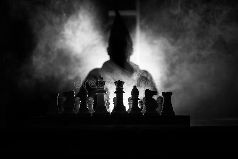homem que joga a xadrez A silhueta borrada assustador de uma pessoa no tabuleiro de xadrez com xadrez figura Fundo nevoento tonif fotografia de stock
