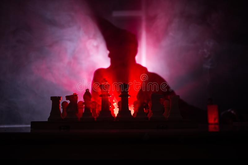 homem que joga a xadrez A silhueta borrada assustador de uma pessoa no tabuleiro de xadrez com xadrez figura Fundo nevoento tonif fotos de stock royalty free