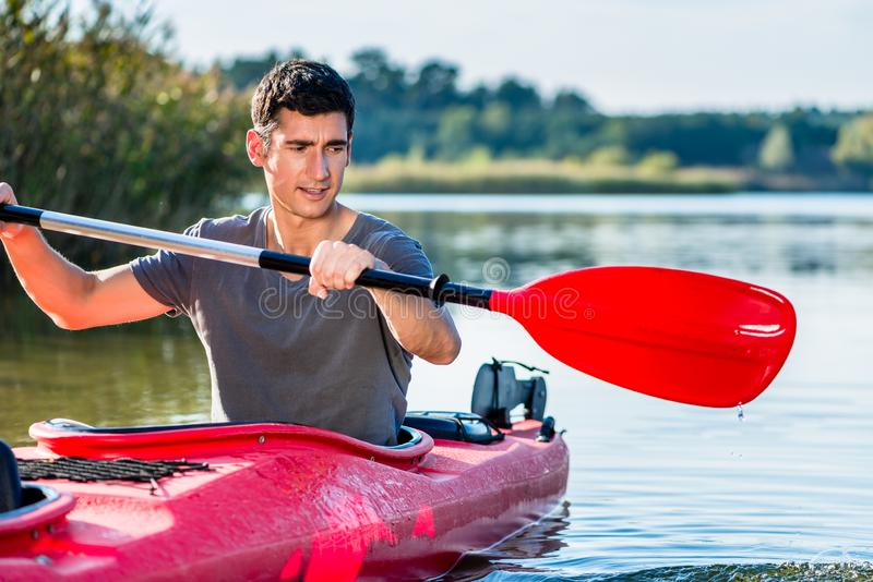 Homem que kayaking no lago fotografia de stock royalty free