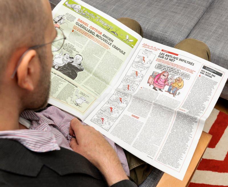 Homem que lê Charlie Hebdo sobre Daniel Ortega imagem de stock royalty free