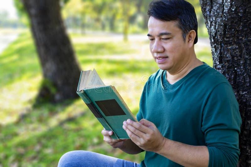 Homem que lê um livro de texto com a cara de sorriso que aprecia no parque fotografia de stock royalty free