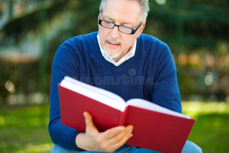 Homem que lê um livro no parque imagens de stock royalty free