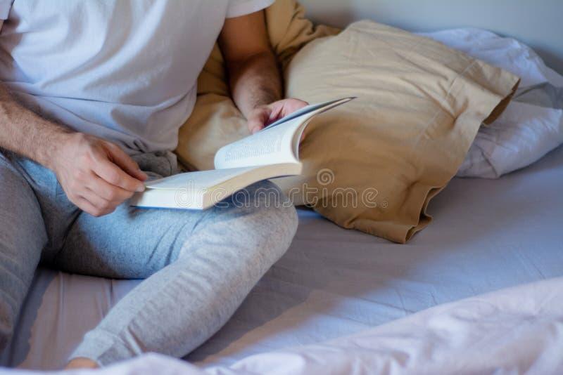 Homem que l? um livro na cama fotos de stock