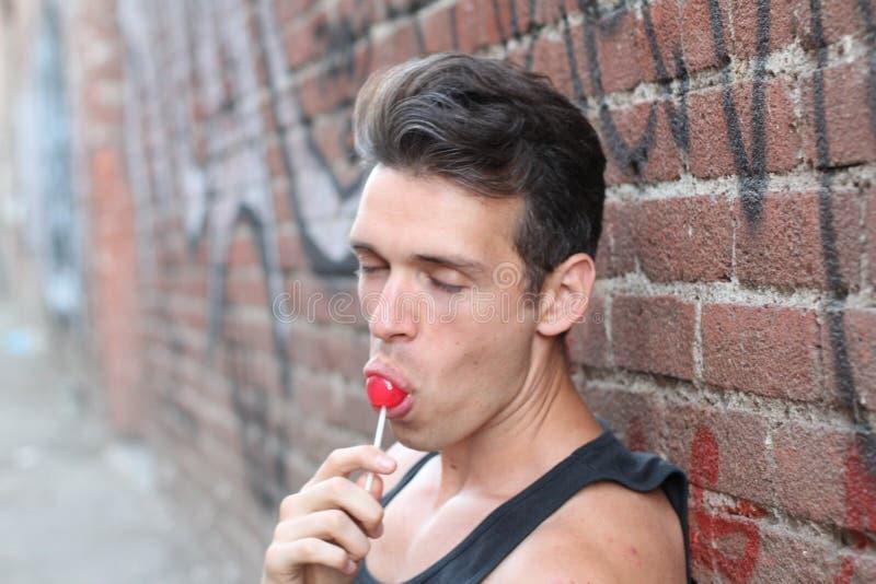 Homem que lambe o close up doce dos doces de açúcar fora imagem de stock