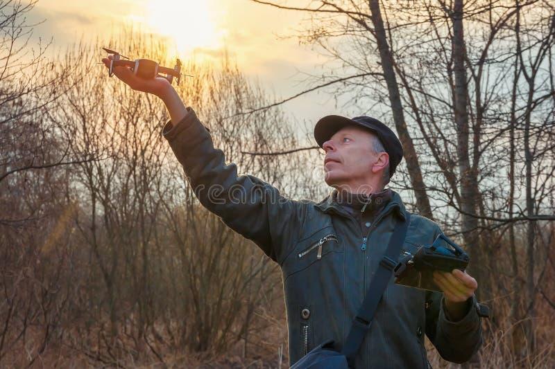 Homem que lança um zangão contra o sol de aumentação foto de stock