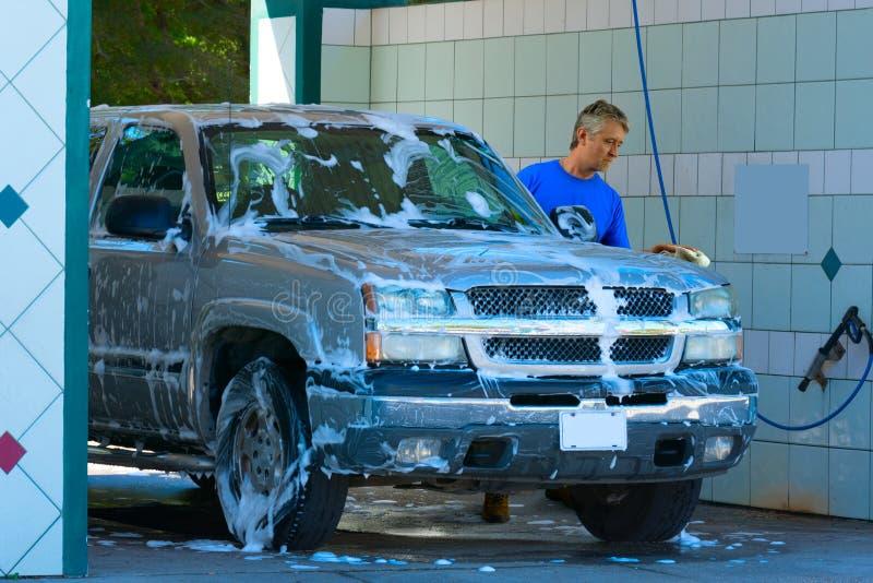 Homem que lava e que esfrega o veículo ensaboado do caminhão imagem de stock
