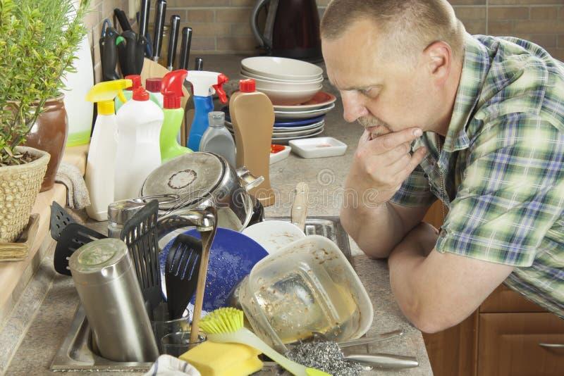 Homem que lava pratos sujos na banca da cozinha imagem de stock royalty free