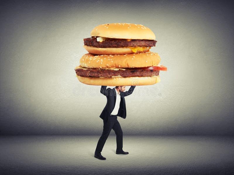 Homem que leva sanduíches grandes imagens de stock