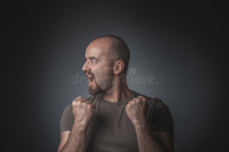Homem que levanta como um vencedor e com uma cabeça no perfil Tiro do est?dio foto de stock